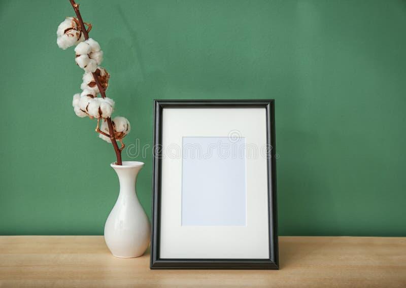 Flores del marco y del algodón de la foto en florero en la tabla contra fondo del color imágenes de archivo libres de regalías