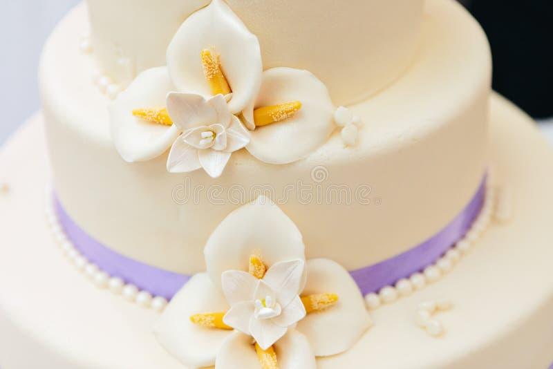 Flores del mazapán y cinta púrpura en el pastel de bodas imagen de archivo