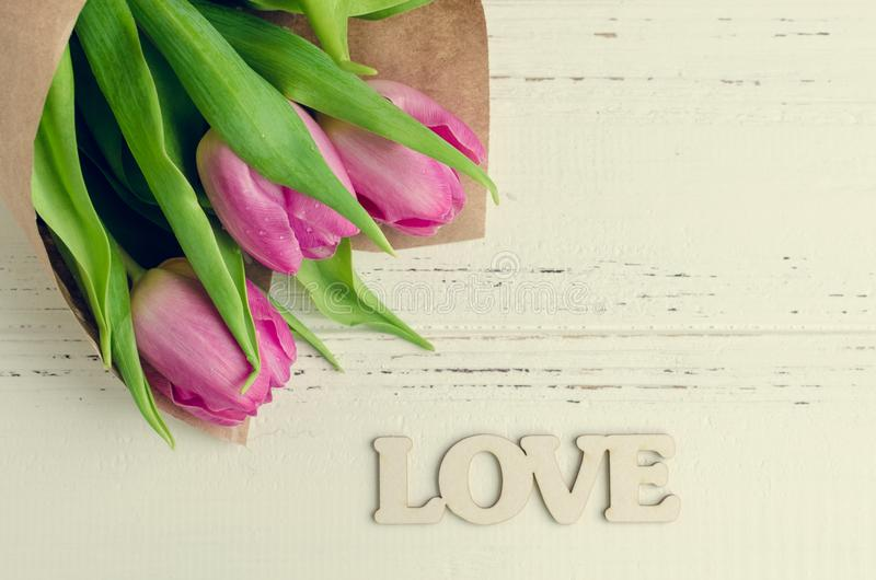 Flores del tulipán con la palabra de madera AMOR fotografía de archivo