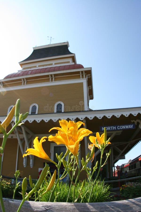 Flores delante de una estación de tren en Conway del norte, New Hampshire fotografía de archivo