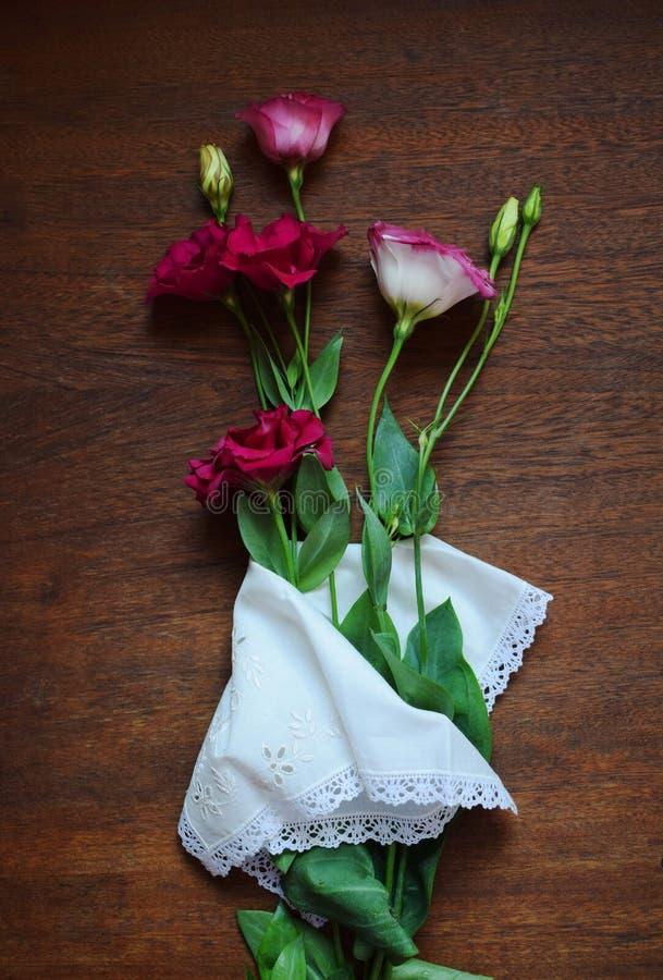 Flores delicadas de Lisianthus del Eustoma y un pañuelo blanco en un fondo de madera oscuro imagenes de archivo