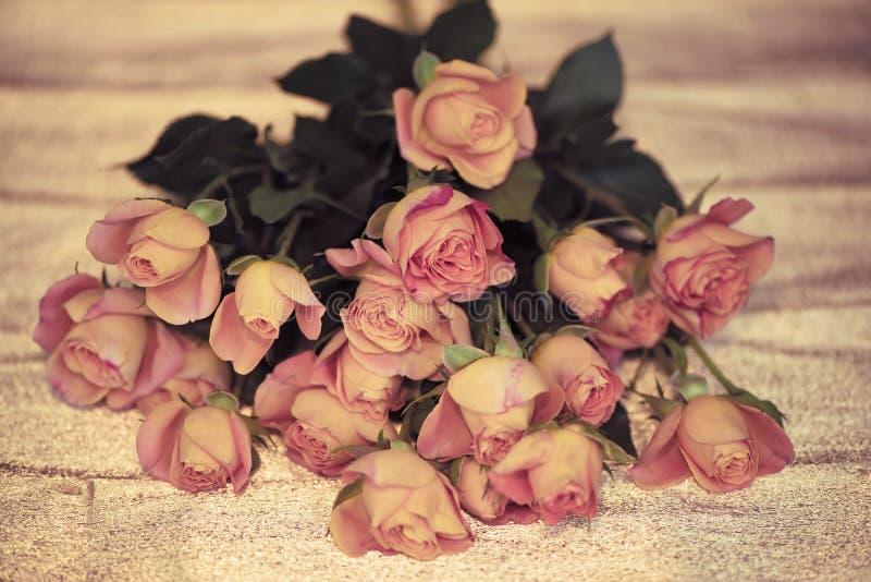 Flores delicadas rosadas de las rosas en fondo de papel de oro Para primavera que espera Tarjeta de pascua feliz foto de archivo