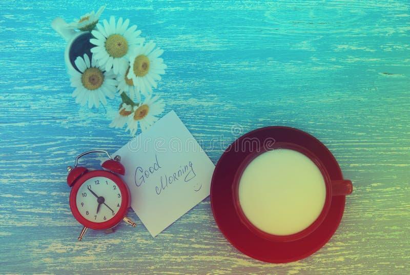 Flores, despertador e copo da margarida do leite com nota do bom dia no fundo de madeira azul rústico foto de stock