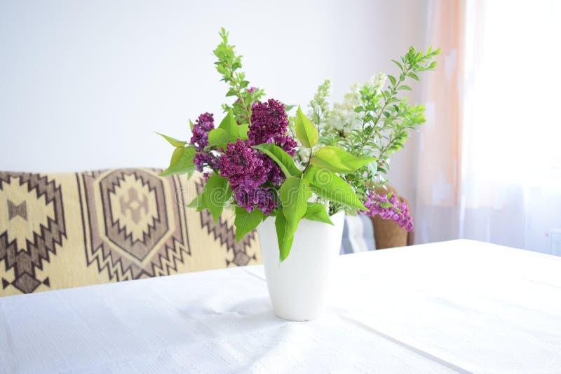 Flores do jardim em um vaso na tabela pela janela fotos de stock royalty free