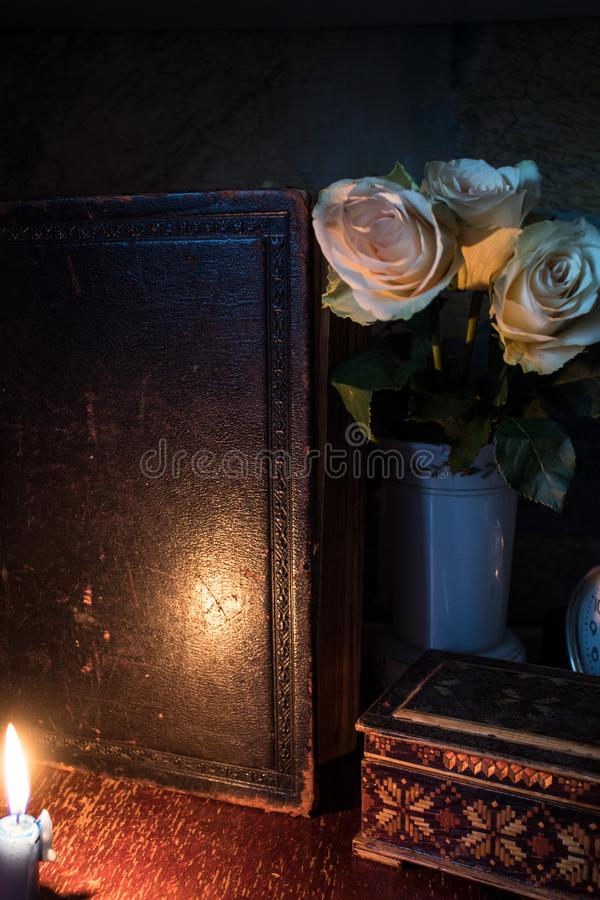 Flores do livro velho e a caixa sob a luz da vela imagens de stock