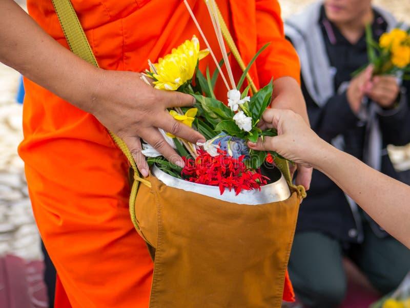Flores do sacrifício da oferta à monge imagens de stock