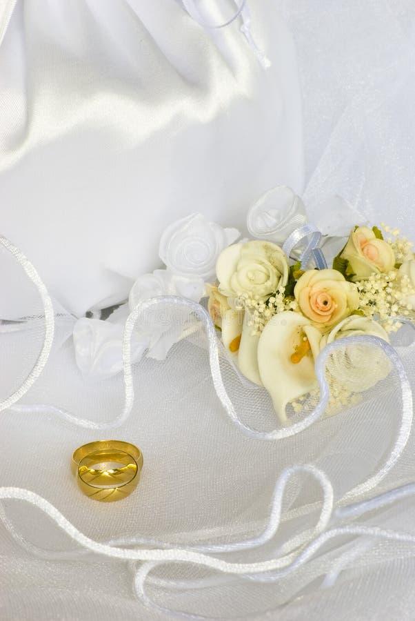 Flores dos anéis de casamento e saco nupcial sobre o véu imagem de stock royalty free