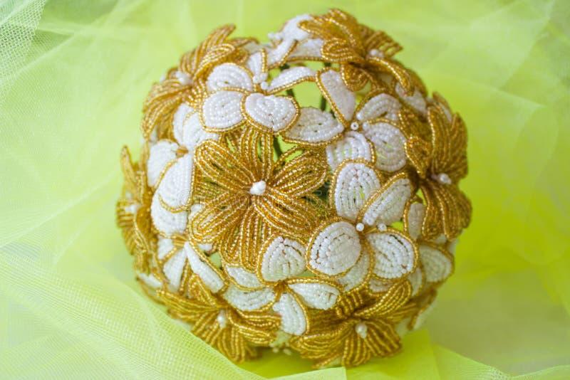 Flores douradas e brancas do ramalhete do casamento dos grânulos Em um fundo borrado amarelo imagens de stock royalty free