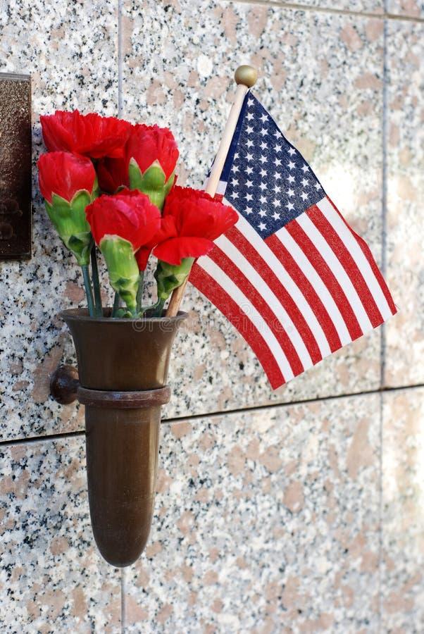 Flores e bandeira americana na cripta foto de stock