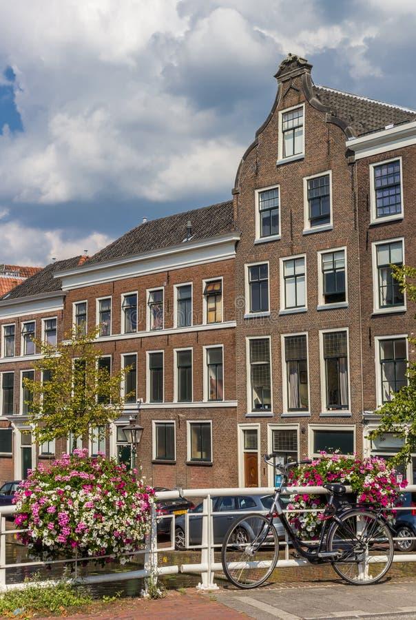 Flores e bicicleta em uma ponte sobre um canal histórico em Leiden imagem de stock