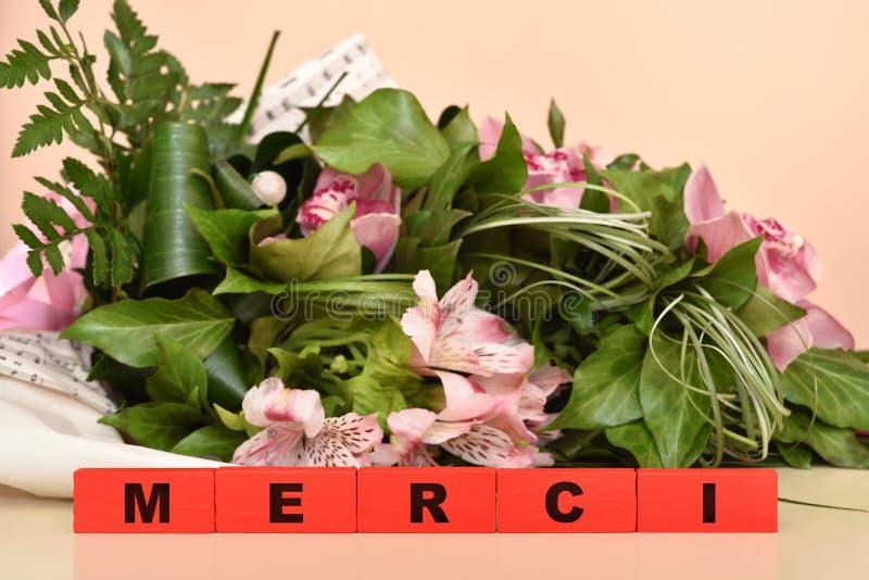 Flores e blocos de madeira vermelhos com mensagem de Merci imagem de stock