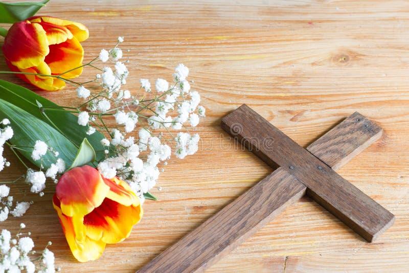 Flores e cruz de easter da mola no fundo de madeira imagem de stock royalty free