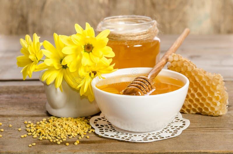 Flores e produtos da abelha & x28 amarelos; mel, pólen, honeycombs& x29; imagem de stock