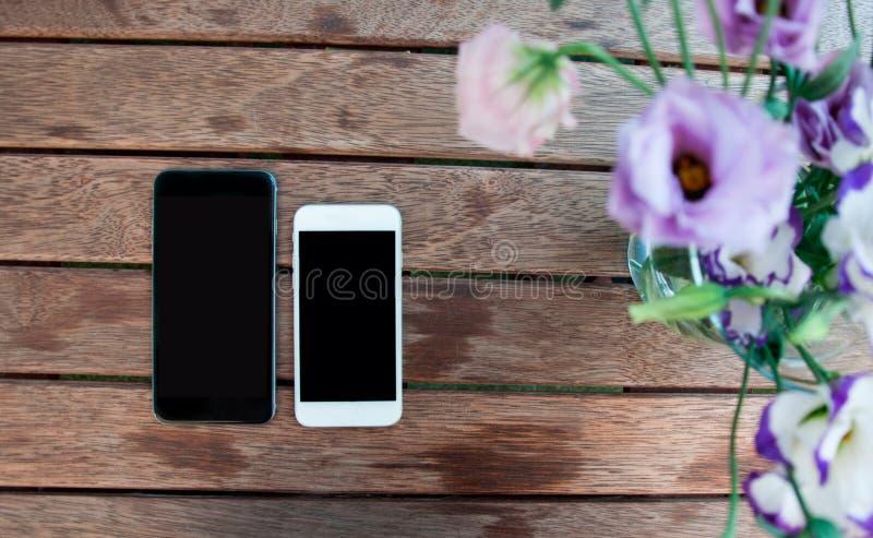 Flores e telefones espertos na tabela de madeira fotos de stock