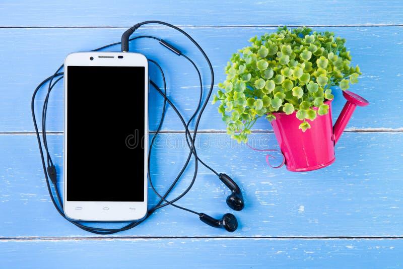 Flores elegantes del teléfono y del plástico en el fondo de madera azul imagen de archivo