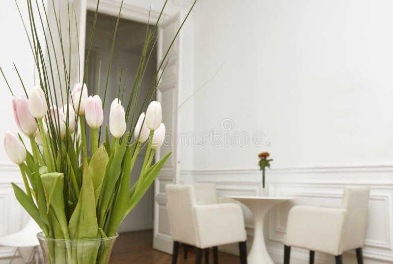 Flores em um interior da casa da sala branca fotos de stock royalty free