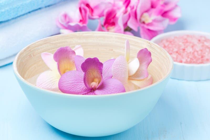 Flores em uma bacia azul, toalhas, sal do mar para termas fotos de stock royalty free