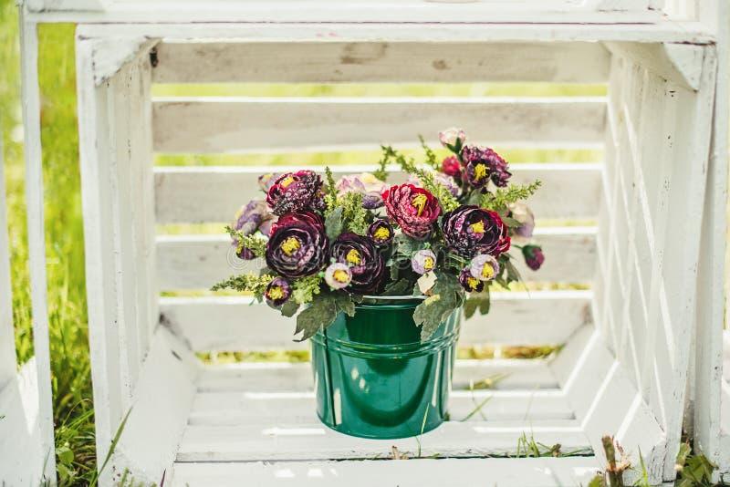 Flores em uma cubeta verde fotografia de stock royalty free