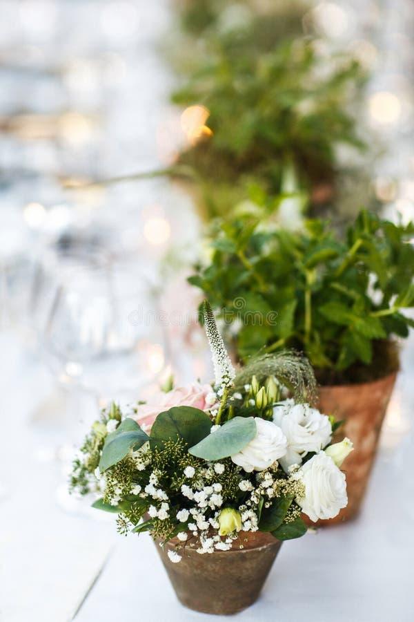 Flores em uns potenciômetros na tabela do weddign Casa de campo italiana fotos de stock
