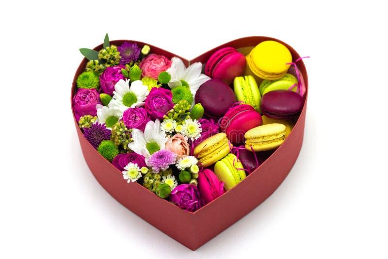 Flores en caja con los macarrones en el fondo blanco foto de archivo