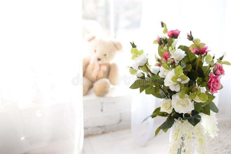Flores en el florero en piso de madera con el muro de cemento para el fondo imagen de archivo