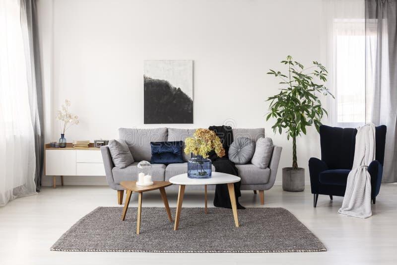 Flores en florero de cristal azul y dos velas blancas en las mesas de centro de madera en sala de estar elegante gris con el sof? imagenes de archivo