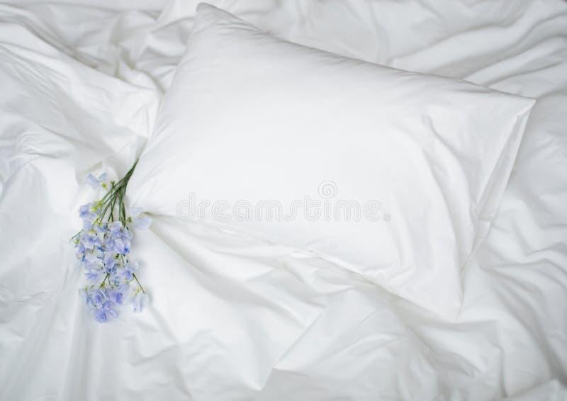 Flores en la cama sucia, los artículos blancos del lecho y el bouqet azul de las flores foto de archivo libre de regalías