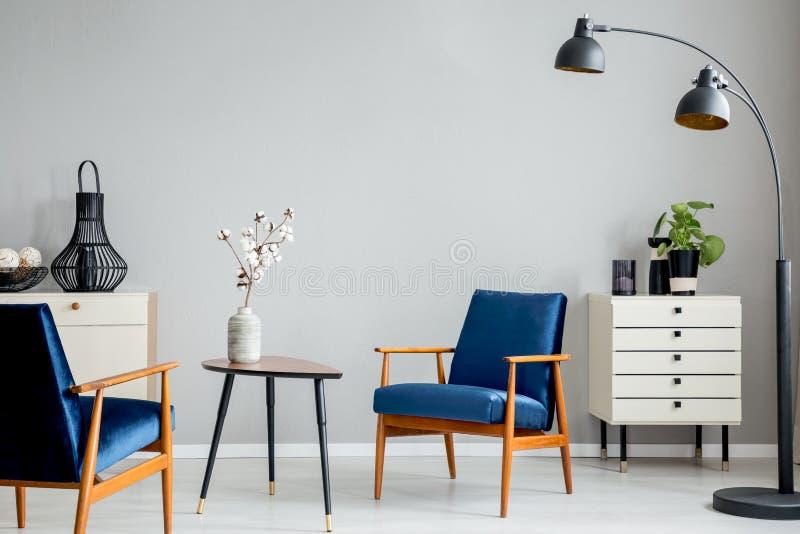 Flores en la tabla de madera entre las butacas azules en interior plano gris con la lámpara negra fotografía de archivo libre de regalías