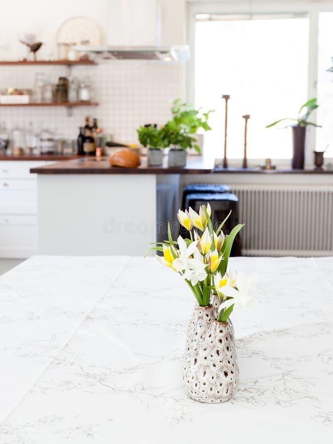 Flores en la tabla en la cocina del primero plano borrosa en el fondo imágenes de archivo libres de regalías