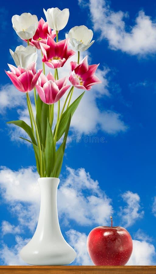 flores en un florero y una manzana en el primer de la tabla fotografía de archivo