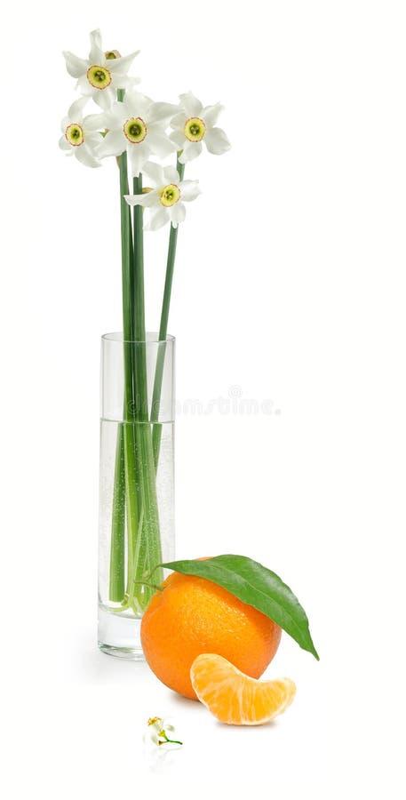 Flores en un florero y una naranja fotografía de archivo libre de regalías