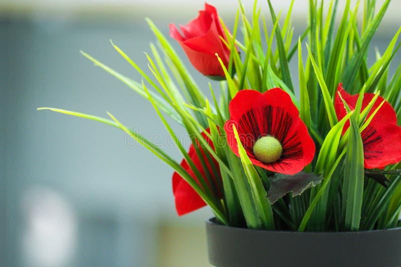 Flores falsas en pote negro fotografía de archivo libre de regalías