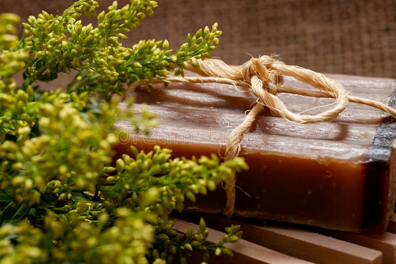 Flores frescas de la solidago del aster, tenedor de madera del jabón e incienso y jabón de barra hechos a mano de la leche de Myr foto de archivo