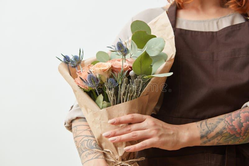 Flores frescas que viven las rosas y el eryngium coralinos como para felicitar el ramo en la mano de la muchacha con el tatuaje,  imagen de archivo libre de regalías