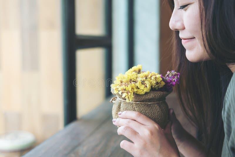 Flores guardando e de cheiro de uma mulher bonita com sentimento feliz imagens de stock