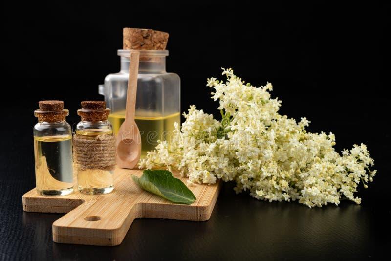 Flores hermosas de la baya del saúco y del jugo medicinal en una botella Remedios caseros naturales para los fríos imagen de archivo