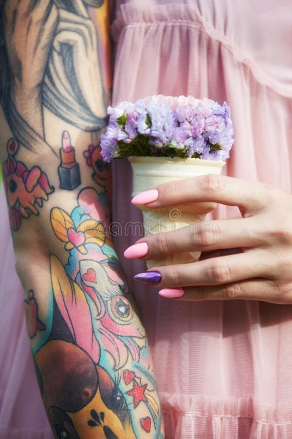Flores hermosas en las manos de una muchacha con los tatuajes, cosméticos Flores del verano y maquillaje brillante en los clavos  fotografía de archivo libre de regalías