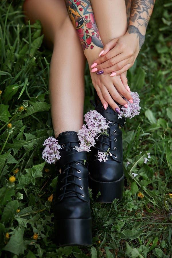 Flores hermosas en las manos de una muchacha con los tatuajes, cosméticos Flores del verano y maquillaje brillante en los clavos  fotos de archivo libres de regalías
