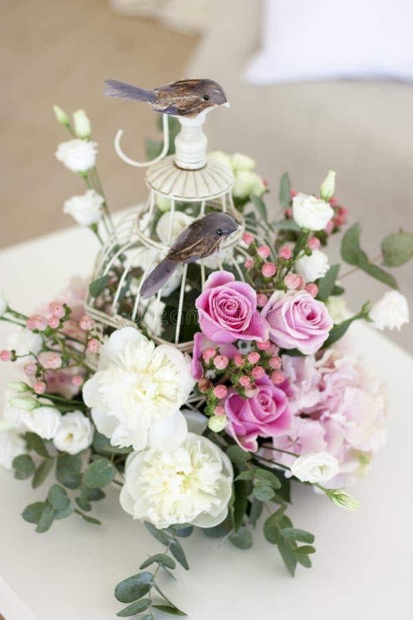 Flores hermosas en una jaula blanca decorativa con un pájaro Ramo original imagen de archivo libre de regalías