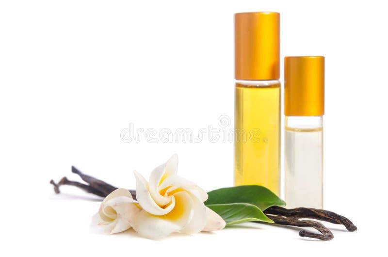 Flores hermosas, vainilla natural y botellas con los aceites para la piel foto de archivo libre de regalías