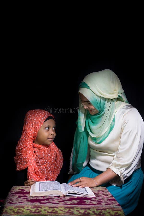 FLORES, 25 INDONESI?-JUNI 2014: Een hijabzuster onderwijst haar zuster die ook een hijab draagt om quran op een lijst met te leze stock afbeeldingen