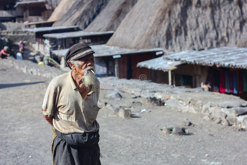 FLORES/INDONESIA- 6 DE NOVIEMBRE DE 2012: Un paisaje de un pueblo viejo llamó el pueblo de Bena en Flores y a un abuelo vestido e foto de archivo libre de regalías