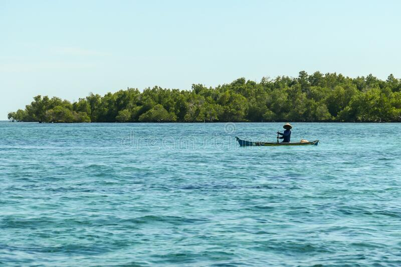Flores/Indonesia 20290808: A fisherman`s boat crossing a calm sea near Maumere, Indonesia There is one man in the boat, wearing. Straw hat and paddling. There stock photo