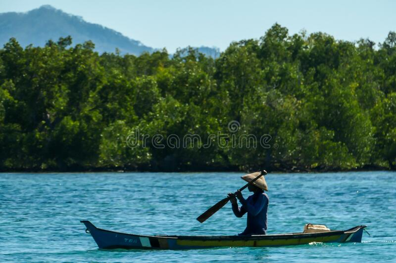 Flores/Indonesia 20290808: A fisherman`s boat crossing a calm sea near Maumere, Indonesia There is one man in the boat, wearing. Straw hat and paddling. There royalty free stock image