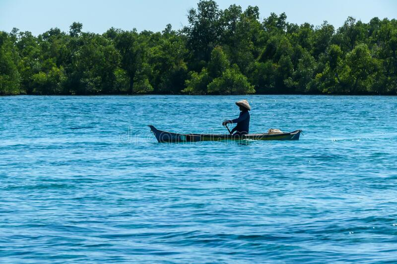 Flores/Indonesia 20290808: A fisherman`s boat crossing a calm sea near Maumere, Indonesia There is one man in the boat, wearing. Straw hat and paddling. There royalty free stock images