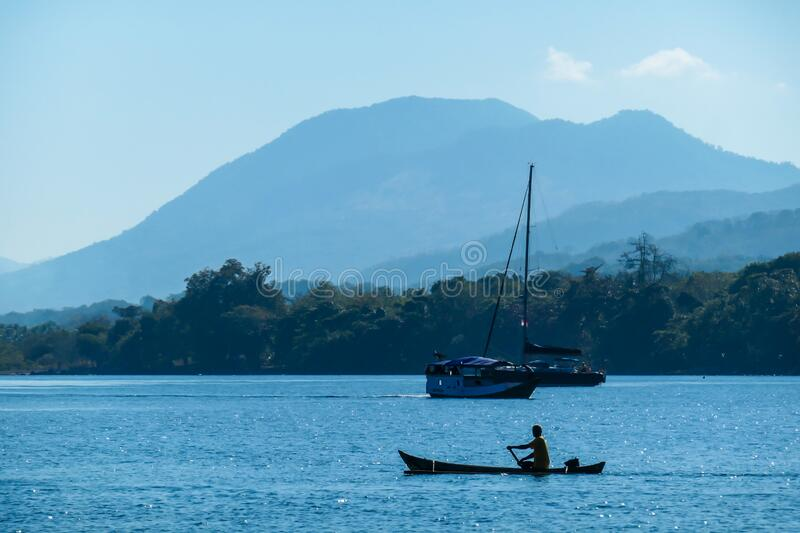Flores/Indonesia 20290808: A fisherman`s boat crossing sea near Maumere, Indonesia There is one man in the boat, wearing straw ha. T and paddling. There is a stock photo
