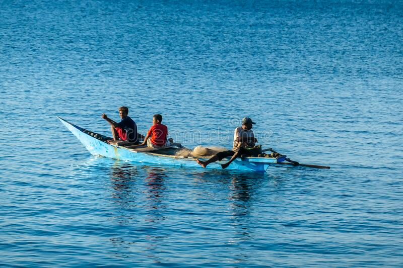 Flores/Indonesia 20290808: A fishermen`s boat crossing a calm sea near Maumere, Indonesia There are three men in one small, blue. Boat, one of them is paddling stock photo