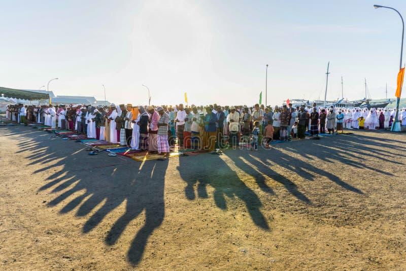 FLORES/INDONESIA-, 28. JULI 2014: Moslems beten zum Feiern von Eid al-Fitr, das das Ende des Monats von Ramadan am Hafen markiert stockfotos