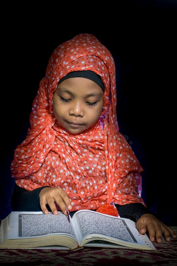 FLORES, INDONESIA-JUNE 25 2014: Dziewczyna jest ubranym hijab wokoło 7 lat czyta koran na stole z etnicznymi motywami zdjęcia royalty free