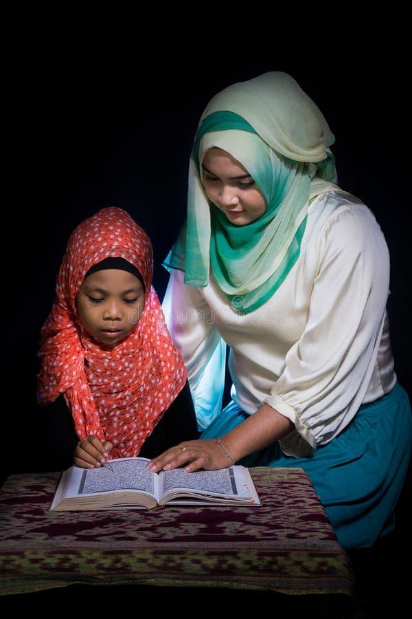 FLORES INDONESIA-JUNE 25 2014: En hijabsyster undervisar hennes syster som bär också en hijab för att läsa quranen på en tabell m royaltyfri foto